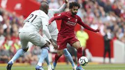Penyerang Liverpool, Mohamed Salah, berusaha melewati pemain West Ham pada laga Premier League di Stadion Anfield, Minggu (12/8/2018). Liverpool menang 4-0 atas West Ham. (AP/David Davies)