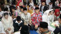 Gubernur DKI Jakarta, Anies Baswedan dan Wagub Sandiaga Uno saat meninjau nikah massal di malam pergantian tahun di Jalan MH Thamrin, Jakarta, Minggu (31/12).  Sebanyak 430 pasangan melakukan nikah massal. (Liputan6.com/Angga Yuniar)