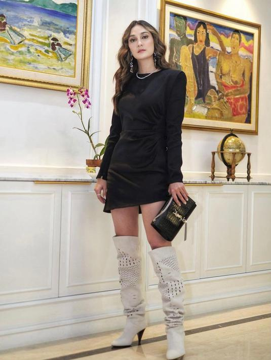 Mini dress warna hitam yang dipadukan dengan over the knee boots buat lookmu semakin terlihat elegan dan berkelas. (Instagram/lunamaya).