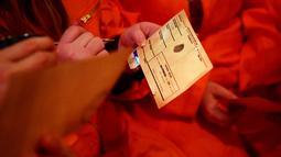 Para tamu mengisi formulir yang mengungkapkan kejahatan mereka saat mengunjungi bar koktail Alcotraz  di London , 11 Oktober 2018. Bar unik berkonsep penjara ini membuat pengunjung merasakan sensasi menjadi narapidana. (BEN STANSALL / AFP)