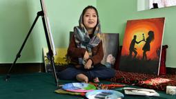 Seniman Robaba Mohammadi duduk di sebelah lukisannya selama wawancara dengan AFP mulut di studionya di Kabul pada 5 Desember 2019. Melalui lukisan, seniman asal Afghanistan ini mengekspresikan bahwa wanita dan disabilitas bukan lagi hal yang bisa dipandang sebelah mata. (NOORULLAH SHIRZADA/AFP)