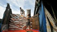 Pekerja memanggul karung Beras dari truk di pasar induk Cipinang, Jakarta, Selasa (27/12). Menteri Perdagangan (Mendag) Enggartiasto Lukita mengatakan, stok kebutuhan pokok pangan hingga akhir tahun akan cukup. (Liputan6.com/Angga Yuniar)