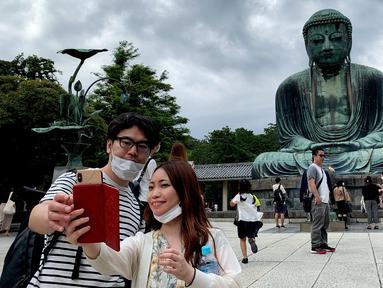 Sepasang pengunjung berswafoto dengan latar belakang The Great Buddha atau yang biasa disebut Kamakura Daibutsu di kuil Kotoku-in di Kamakura, Prefektur Kanagawa, Jepang, Sabtu (20/6/2020). Patung Buddha yang menjulang dengan tinggi 13,35 meter ini didirikan tahun 1252. (Behrouz MEHRI/AFP)