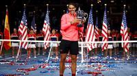 Rafael Nadal memegang trofi AS Terbuka 2017 setelah mengalahkan Kevin Anderson di final, Minggu (10/9/2017) waktu setempat. (AP Photo/Peter Morgan)