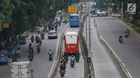 Pengendara motor melaju di belakang bus Transjakarta di kawasan Pasar Rumput, Jakarta, Rabu (20/2). PT Transportasi Jakarta akan memasang kamera pengawas (CCTV) di setiap halte untuk menerapkan tilang online atau E-Tilang. (Liputan6.com/Immanuel Antonius)