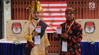 Petugas KPPS memegang surat suara pelaksanaan Pilkada Serentak 2018 di TPS XII Kelurahan Sei Mati, Kecamatan Medan Maimun, Rabu (27/6). Baju adat dari berbagai daerah dan suku tampak dikenakan oleh petugas TPS. (Liputan6.com/Reza Perdana)