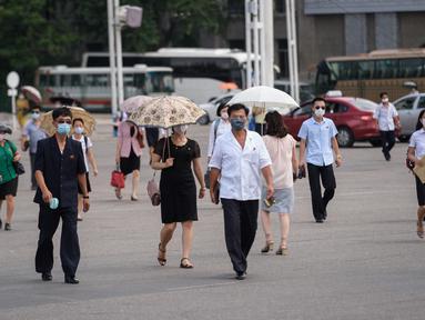 Pejalan kaki melewati alun-alun saat suhu tinggi mencapai 34 derajat celsius di Pyonyang, Korea Utara, Rabu (21/7/2021). Musim Panas dimulai pada bulan Juni hingga Agustus, dan puncak musim panas adalah bulan Agustus. (KIM Won Jin / AFP)