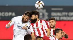 Bek Real Madrid, Sergio Ramos (kiri) berduel udara dengan striker Athletic Bilbao, Asier Villalibre dalam laga semifinal Piala Super Spanyol 2020/21 di La Rosaleda Stadium, Malaga, Kamis (14/1/2021). Real Madrid kalah 1-2 dari Athletic Bilbao. (AFP/Jorge Guerrero)