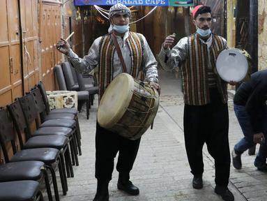 """Pria Palestina yang dikenal dengan """"Musaharatis"""" saat bertugas sebagai """"penabuh drum Ramadhan"""" di kota tua Hebron, Tepi Barat pada 14 April 2021. Mereka menyusuri jalan-jalan kota, masuk ke gang-gang kecil untuk membangunkan umat Islam sahur selama bulan Ramadhan. (HAZEM BADER/AFP)"""