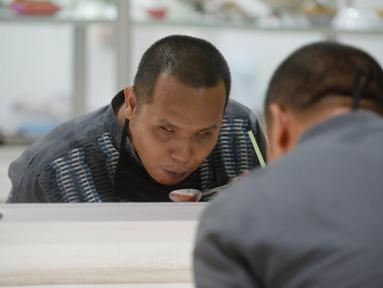 Pengunjung tuna netra menyantap makanan di Warteg FAST, Graha Raya Bintaro, Tangerang Selatan, Banten, Kamis (3/12/2020). Warteg FIST setiap hari membagikan makan gratis bagi penyandang Disabilitas, Tuna Netra serta Ibu Hamil yang datang kewarung. (merdeka.com/Dwi Narwoko)