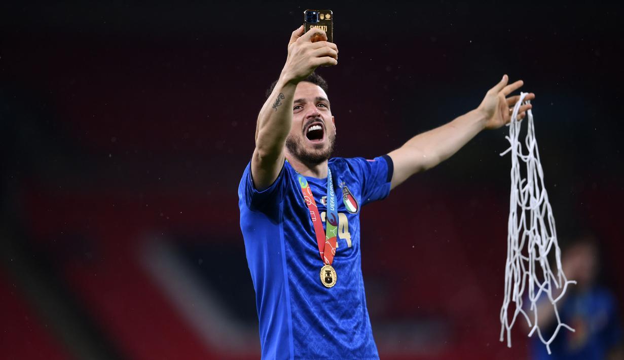 Alessandro Florenzi memamerkan potongan jaring gawang Stadion Wembley lewat ponselnya usai Italia menangkan pertandingan Final Euro melawan Inggris. (Foto: AP/Pool/Laurence Griffiths)