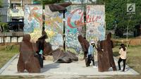 Pengunjung berfoto di depan Tembok Berlin di area RTH Kalijodo, Rabu (20/6). Banyaknya pilihan permainan buat anak-anak menjadikan RTH Kalijodo memiliki daya tersendiri untuk menghabiskan waktu libur bersama keluarga. (Lipiutan6.com/Helmi Fithriansyah)