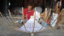 Seorang perajin membuat payung kertas di Desa Tanjung, Kecamatan Juwiring, Klaten, Kamis (11/10). Para perajin menjadikan usaha payung hias sebagai tulang punggung ekonomi keluarga. (Liputan6.com/Gholib)