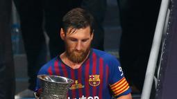 Penyerang Barcelona, Lionel Messi membawa Piala Super Spanyol usai mengalahkan Sevilla di Tangier, Maroko, (13/8). Barcelona meraih gelar ke-13 di Piala Super Spanyol terbanyak ketimbang tim lain. (AP Photo/Mosa'ab Elshamy)