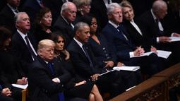 Presiden AS Donald Trump duduk bersebelahan dengan mantan presiden Barack Obama, mantan presiden Bill Clinton dan mantan presiden Jimmy Carter dalam prosesi pemakaman kenegaraan George HW Bush di Washington, Rabu (5/12). (Brendan SMIALOWSKI/AFP)