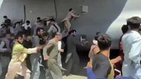 Ratusan orang berusaha menaiki pesawat angkut C-17 Angkatan Udara AS di landasan bandara internasional, di Kabul, Afghanistan (16/8/2021).  Di tengah kekacauan pasca direbutnya Ibukota Kabul oleh pasukan Taliban, dua warga jatuh dari pesawat militer Amerika Serikat. (Verified UGC via AP)