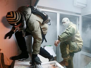 Dua orang demonstran saat merusak seisi bank Rusia, Sberbank di Kiev, Ukraina (21/11). Aksi dilakukan untuk memperingati tragedi kerusuhan 2014 yang menyebabkan lebih dari 100 warga Ukraina tewas. (REUTERS/Valentyn Ogirenko)