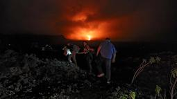 Warga berjalan kaki menaiki lereng untuk melihat guguran lava pijar yang keluar dari gunung api Piton de la Fournaise atau Peak of the Furnace di Pulau Reunion, Samudera Hindia, Prancis, Selasa (13/8/2019). Letusan Piton de la Fournaise berlanjut hingga hari ketiga. (Richard BOUHET/AFP)