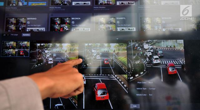Petugas kepolisian menunjukkan rekaman kamera pemantau saat peluncuran Electronic Traffic Law Enforcement (ETLE) di kawasan Bundaran HI, Jakarta, Minggu (25/11). ETLE merupakan sistem penegakan hukum bidang lalu lintas. (Merdeka.com/Iqbal Nugroho)