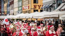Santa claus mengikuti pawai yang merupakan bagian dari Kongres Dunia Sinterklas di Kopenhagen, Denmark, Senin (23/7). Kegiatan sejak 1957  itu merupakan forum pertemuan nyata ratusan santa dari seluruh dunia. (Mads Claus Rasmussen/Ritzau Scanpix /AFP)