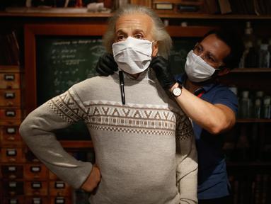 Seorang pekerja mengenakan makser pada patung lilin sosok Albert Einstein di Madame Tussauds di Istanbul, Sabtu (11/7/2020). Dibuka kembali, sejumlah sosok tokoh terkenal di museum itu dipakaikan masker untuk meningkatkan kesadaran terhadap penyebaran Covid-19. (AP Photo/Emrah Gurel)