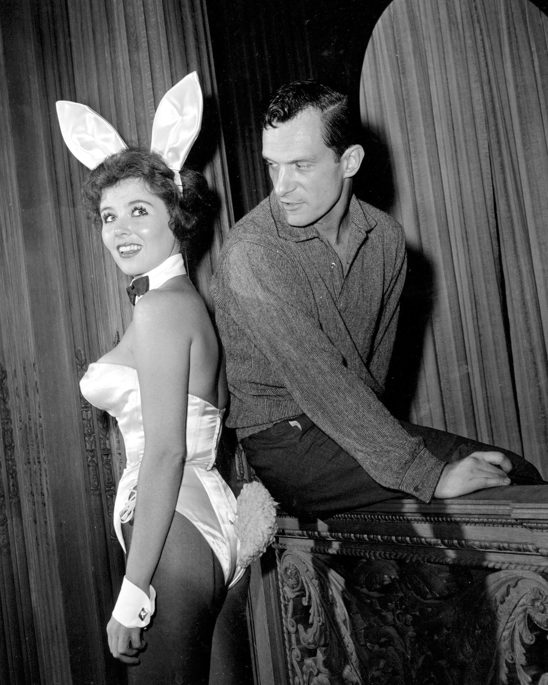 Hugh Hefner berpose dengan seorang wanita di klub malam Hefner, Chicago, pada 20 Juni 1961. Sebelum mendirikan Playboy, Hefner bergabung menjadi tentara dan bekerja sebagai penulis surat kabar militer AS selama dua tahun. (AP Photo/Edward s. Kitch)
