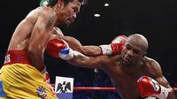 Aksi Floyd Mayweather Jr. saat mengalahkan Manny Pacquiao di MGM Grand Garden Arena, AS, Sabtu (2/5/2015). Menurut data media Forbes setiap tahun Mayweather membukukan penghasilan sebesar 300 miliar dollar AS. (AFP Photo/John Gurzinksi)