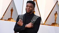 Aktor Chadwick Boseman berpose di karpet merah ajang Piala Oscar 2018, Los Angeles, Minggu (4/3). Pemeran utama Black Panther ini tampil bak raja dengan jas hitam dengan aksen perak yang melintang di bagian dada. (Jordan Strauss/Invision/AP)