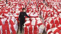 Petugas memeriksa bantuan paket sembako dari Presiden Joko Widodo di Tangerang, Sabtu (9/6/2020). Ribuan paket sembako tersebut akan didistribusikan kepada warga kurang mampu di wilayah Bodetabek guna mengurangi beban ekonomi mereka di tengah pandemi COVID-19. (Liputan6.com/Angga Yuniar)