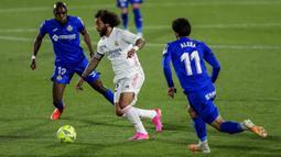 Pemain Real Madrid Marcelo (tengah) menggiring bola melewati pemain Getafe Alena (kanan) dan Allan Nyom (kiri) pada pertandingan Liga Spanyol di Stadion Alfonso Perez, Getafe, Spanyol, Minggu (18/42021). Pertandingan berakhir dengan skor 0-0. (AP Photo/Manu Fernandez)