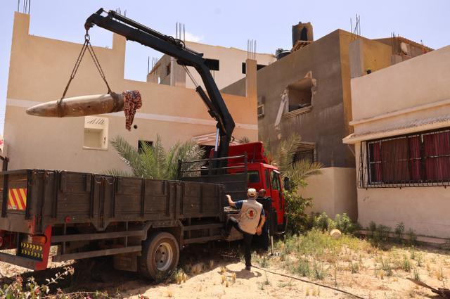 Pakar peledak Hamas dibantu dengan kendaraan saat mengeluarkan rudal Israel yang tidak meledak dari sebuah rumah di Khan Yunis, Jalur Gaza selatan (20/5/2021). (AFP/Said Khatib)