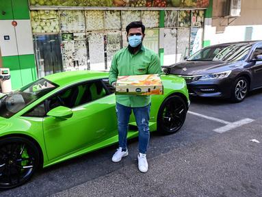 Direktur Pelaksana Pakistan Supermarket Dubai Muhammad Jehanzeb berdiri dekat Lamborghini Huracan sebelum mengirim pesanan mangga di Dubai, Uni Emirat Arab, Kamis (2/7/2020). Supermarket tersebut mengantarkan pesanan mangga untuk minimal pesanan sekitar USD 27. (CACACE GIUSEPPE/AFP)