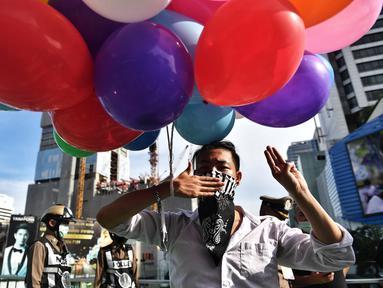 Seorang pengunjuk rasa memegang seikat balon sambil memberi hormat pada Hunger Games dengan tiga jari selama protes terhadap usulan pembelian kapal selam oleh Perdana Menteri Thailand Prayut Chan-O-Cha yang berpihak pada militer di Bangkok (31/8/2020). (AFP/Lillian Suwanrumpha)