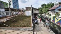 Anak-anak bermain dekat pembangunan Taman Maju Bersama (TMB) Simpang UKU di kawasan Utan Kayu, Jakarta Timur, Senin (6/9/2021). Suku Dinas Pertamanan dan Hutan Kota Jakarta Timur membangun TMB Simpang UKU yang mengusung konsep taman kantong (pocket park). (merdeka.com/Iqbal S. Nugroho)