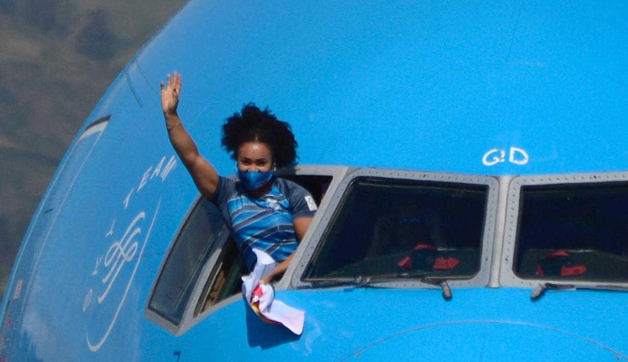 Lifter peraih medali emas, Neisi Patricia Dajomes Barrera melambaikan tangan dari ruang kokpit pesawat saat tiba di bandara Kota Equito, Ekuador, Rabu (4/8/2021). Neisi Patricia berhasil meraih medali emas usai berhasil juara angkat besi 76kg putri di Olimpiade Tokyo 2020. (AFP/Rodrigo Buendia)