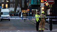 Polisi berbincang dengan petugas pemadam kebakaran saat penemuan bom Perang Dunia II di kawasan Soho, London, Inggris, Senin (3/2/2020). Polisi mengevakuasi warga yang berada di kafe, restoran, pub, dan kantor radius beberapa blok dari lokasi penemuan bom. (AP Photo/Frank Augstein)