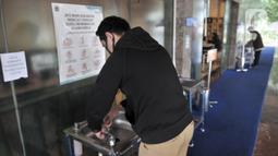 Pegawai mencuci tangan sebelum memasuki gedung Balai Kota pada hari pertama kerja di tengah pembatasan sosial berskala besar (PSBB) masa transisi di Jakarta, Senin (8/6/2020). PNS di lingkungan Pemprov DKI kembali mulai bekerja di kantor dengan sistem shifting. (merdeka.com/Iqbal S Nugroho)