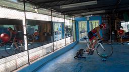 Atlet triathlon Kuba, Leslie Amat mengendarai sepedanya, diadaptasi menjadi stasioner, di bawah pengawasan pelatihnya Dioseles Fernandez di teras rumahnya di Havana, Senin (20/4/2020). Atlet Kuba tak bisa berlatih di fasilitas olahraga seperti biasanya selama pademi corona. (AP /Ismael Francisco)