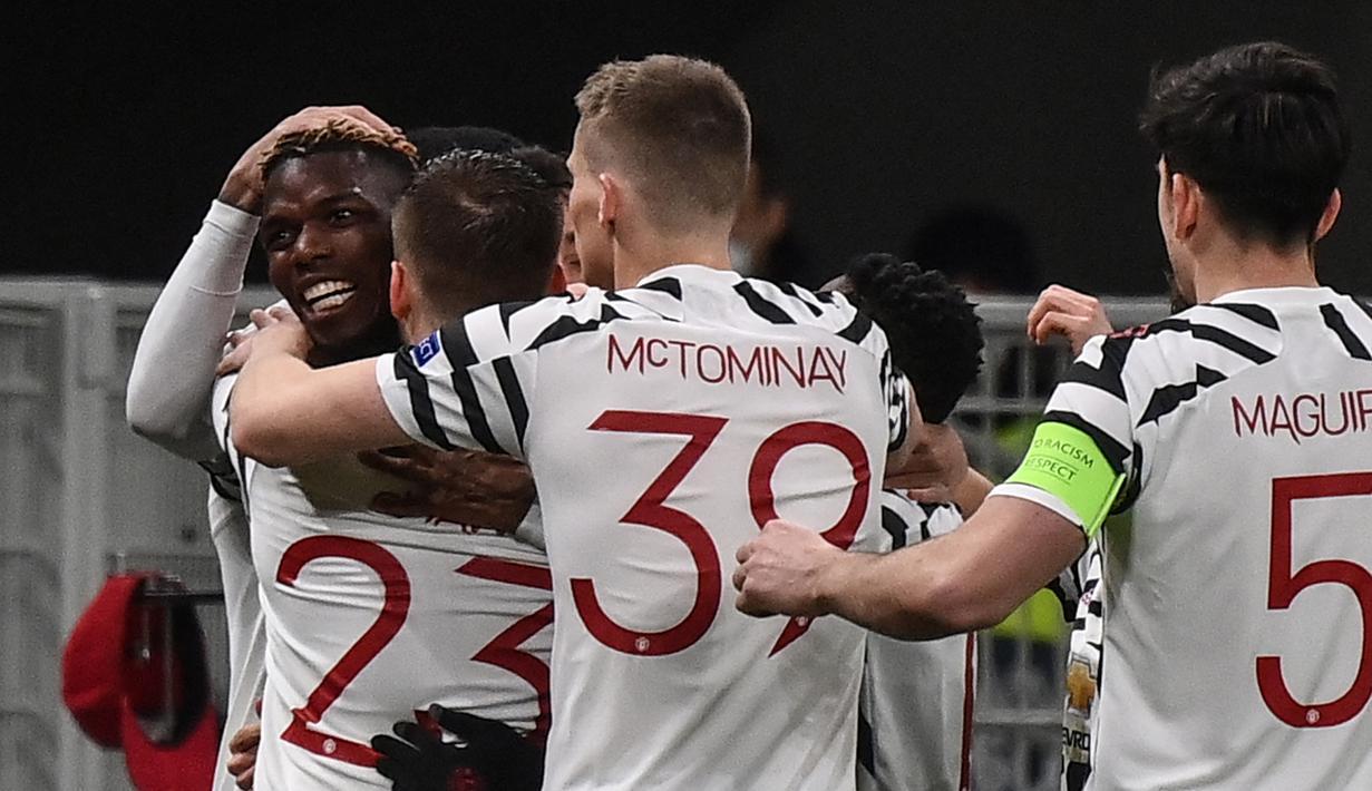 Gelandang Manchester United, Paul Pogba (kiri) bersama rekan setim merayakan gol yang dicetaknya ke gawang AC Milan dalam laga leg kedua babak 16 besar Liga Europa 2020/2021 di San Siro Stadium, Milan, Kamis (18/3/2021). Manchester United menang 1-0 atas AC Milan. (AFP/Marco Bertorello)