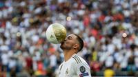 Pemain baru Real Madrid, Eden Hazard mencium bola saat diperkenalkan di stadion Santiago Bernabeu di Madrid, Spanyol (13/6/2019). Real Madrid mengumumkan telahresmi membeli pemain asal Belgia tersebut dari klub Inggris, Chelsea. (AP Photo/Manu Fernandez)