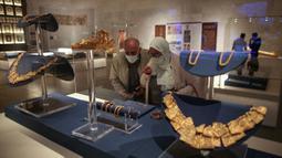 Pengunjung melihat perhiasan kuno yang dipamerkan di Museum Nasional Peradaban Mesir (NMEC), Distrik Fustat, Kairo Lama, Mesir, 4 April 2021. Museum Nasional Peradaban Mesir kembali dibuka sehari setelah upacara Parade Emas Firaun. (Mahmoud KHALED/AFP)