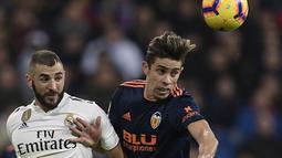 Striker Real Madrid, Karim Benzema, berebut bola dengan bek Valencia, Gabriel Paulista, pada laga La Liga di Stadion Santiago Bernabeu, Madrid, Sabtu (1/12). Madrid menang 2-0 atas Valencia. (AFP/Oscar Del Pozo)