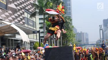 Salah satu pemuda peduli Nias melakukan atraksi lompat batu di kawasan Jalan Jenderal Sudirman, Jakarta, Minggu (4/3). Pemuda Peduli Nias melakukan beragam atraksi budaya untuk mempromosikan pariwisata di pulau tersebut. (Liputan6.com/Helmi Fithriansyah)