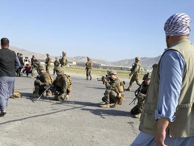 Tentara AS mengambil posisi untuk menjaga di sepanjang perimeter di bandara internasional di Kabul, Afghanistan (16/8/2021). Militer dan pejabat AS fokus di bandara Kabul, di mana ribuan warga Afghanistan terjebak oleh Taliban tiba-tiba. (AP Photo/Shekib Rahmani)