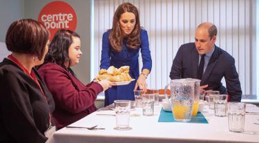 Pangeran William bersama sang istri, Kate Middleton menyajikan makan siang saat mengunjungi Centrepoint di Barnsley, Inggris, Rabu (14/11). Centrepoint merupakan sebuah badan amal yang membantu para tunawisma. (Charlotte Graham / POOL / AFP)