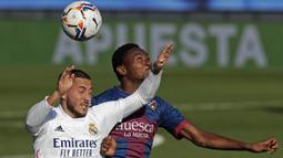 Penyerang Real Madrid, Eden Hazard, berebut bola dengan gelandang Huesca, Kelechi Nwakali, pada laga lanjutan Liga Spanyol di Stadion Alfredo Di Stefano, Sabtu (31/10/2020) malam WIB. Real Madrid menang 4-1 atas Huesca. (AP Photo/Manu Fernandez)