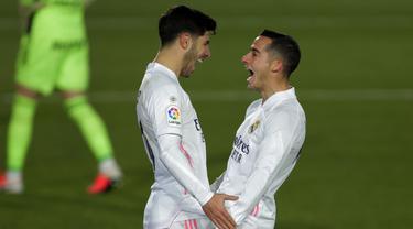 Gelandang Real Madrid, Marco Asensio (kiri) berselebrasi dengan rekannya Lucas Vazquez usai mencetak gol ke gawang Celta Vigo pada pertandingan lanjutan La Liga Spanyol di stadion Alfredo Di Stefano, Minggu (3/1/2021). Madrid menang atas Celta Vigo 2-0. (AP Photo/Manu Fernandez)
