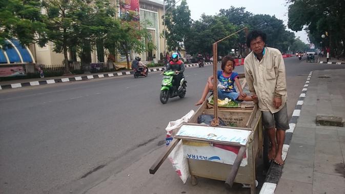Ahmad membawa gerobak kayu bersama istri dan anaknya untuk mengemis di salah satu jalan protokol di Palembang (Liputan6.com / Nefri Inge)