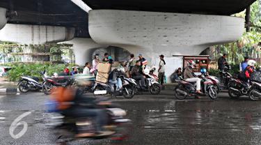Pengendara sepeda motor berteduh di bawah flyover saat hujan turun, Jakarta, Senin (16/11). Memasuki musim hujan, polisi meminta pengendara untuk tidak berteduh di sembarang tempat, khususnya di bawah fly over. (Liputan6.com/Immanuel Antonius)