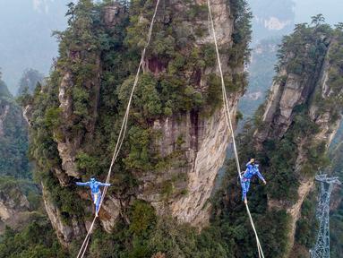 Dua kontestan berpakaian karakter Avatar berpacu sepanjang slackline di Pegunungan Huangshizhai di Zhangjiajie, Hunan, China, Minggu (23/12). Aksi tersebut dilakukan saat mengikuti slackline internasional.  (STR/AFP)